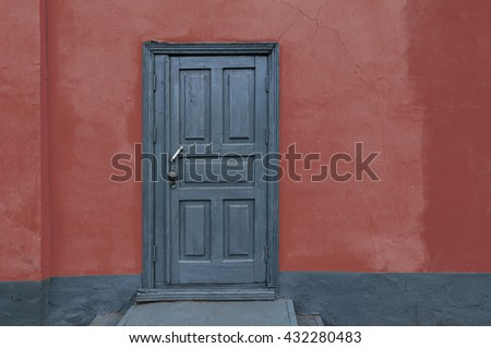 Rustic vintage old house red wall with gray wooden door. Copy scape - stock photo