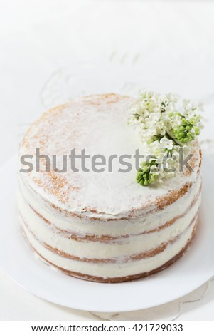 Rustic wedding cake with white lilac, light background, close up, selective focus - stock photo