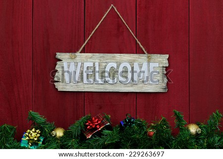 Rustic welcome sign with Christmas garland border and gifts hanging on antique red wooden background - stock photo