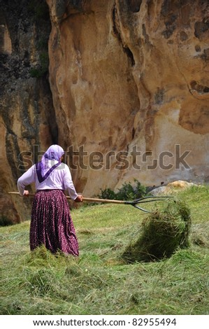 rustic woman working in field (with straws) - stock photo