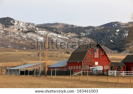 Rustic wooden barn with an American flag in rural Utah, USA. - stock photo