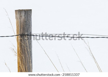 Rustic wooden country fence with snow background  - stock photo