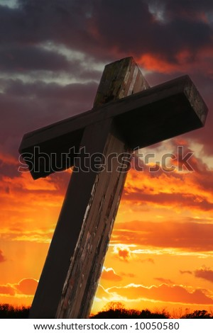Rustic Wooden Cross Against Dramatic Sunset Sky - stock photo
