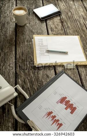 Rustic wooden office desk with statistical report, paperwork with financial graphs, digital tablet and cup of fresh coffee. - stock photo
