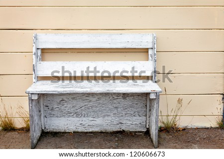 Rustic wooden outdoor cottage bench painted white against a butter yellow wood plank wall. - stock photo