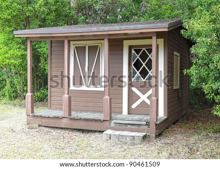 Rustic wooden shed with window and front porch at the edge of the forest - stock photo