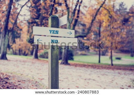Rustic wooden sign in an autumn park with the words Yes - No offering a choice of action and attitude with arrows pointing in opposite directions in a conceptual image. - stock photo
