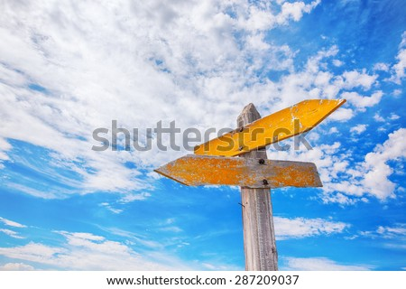 Rustic yellow crossroads sign against a cloudy blue sky. - stock photo