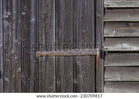 Rusting iron hinges on an old rotting wooden farm door - stock photo