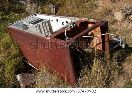 Rusty, abandoned refrigerator lying in a grassy area in a Montana ghost town - stock photo