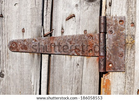 rusty aged iron hinge weathered gray wood door - stock photo