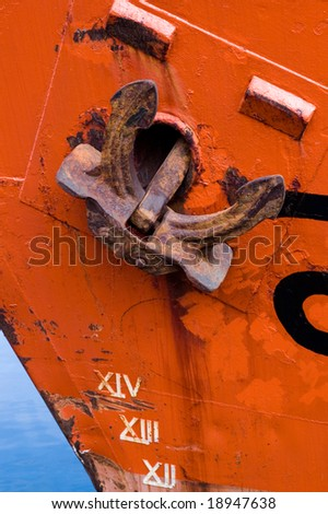 Rusty anchor on orange boat close up - stock photo