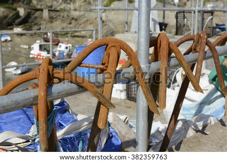 Rusty anchors hanging from railing in Newquay harbour, Cornwall, England - stock photo