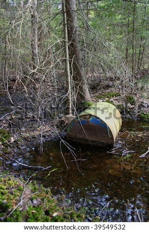 Rusty barrel dumped in swampy forest - stock photo