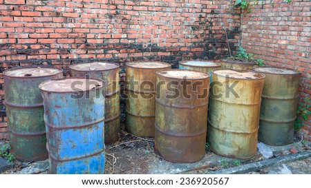 Rusty Barrels  of Green, Blue And Brown Colors Forsaken in The Corner of A Brick Wall.  - stock photo