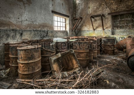 Rusty barrels stored in an abandoned factory, HDR processing - stock photo