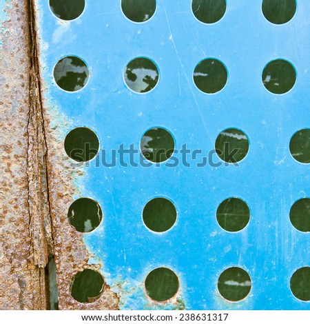 Rusty blue fenestrated metal surface - stock photo