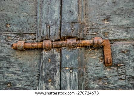 Rusty bolt on wooden door - stock photo