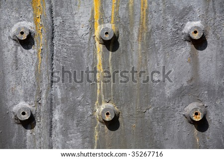Rusty bolts on painted metal plate - stock photo