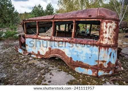 rusty bus on junk yard near Illinci village in Chernobyl Nuclear Power Plant Zone of Alienation, Ukraine - stock photo