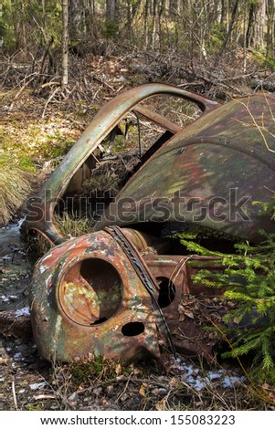 Rusty car wreck in a forrest - stock photo
