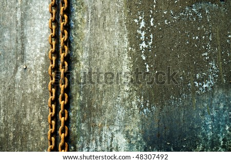Rusty chain hanging on a weathered wall - stock photo