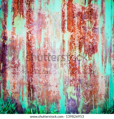 Rusty Colored Metal with cracked paint and green grasses below, grunge background - stock photo