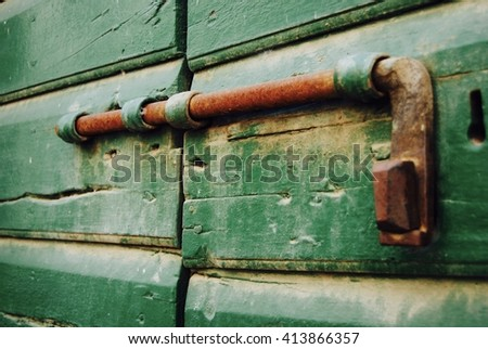 rusty deadbolt latch on green door - stock photo