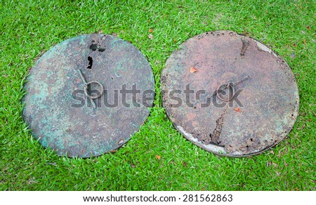Rusty drain cap on the lawn in the urban park. - stock photo