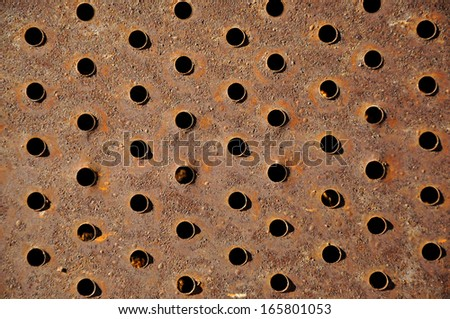Rusty iron background with holes - stock photo