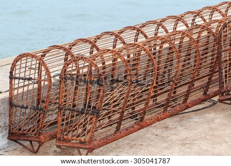 rusty iron basket fishes trap on the pier - stock photo