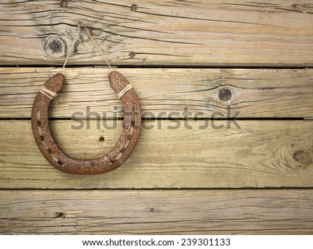 rusty iron horseshoe hung on a nail in an aged knotted wooden wall - stock photo