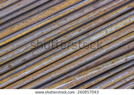 Rusty iron rods used to reinforce concrete. Steel bars background. - stock photo