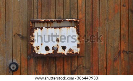 rusty letterbox on a wooden door - stock photo