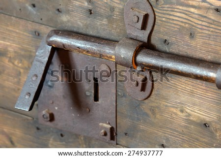 rusty lock with big deadbolt to close the door of the medieval castle - stock photo