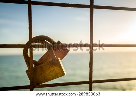 Rusty love locks hanging on the fence as a symbol of loyalty and eternal love - stock photo