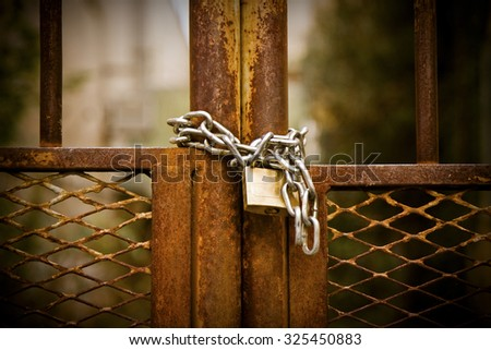 Rusty metal gate closed with padlock - concept image - stock photo