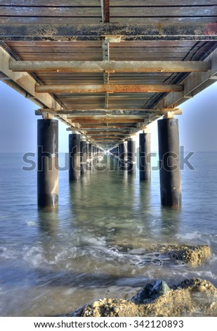 Rusty metallic  pier from sea level in vertical composition creating a diagonal directive tunnel.  - stock photo