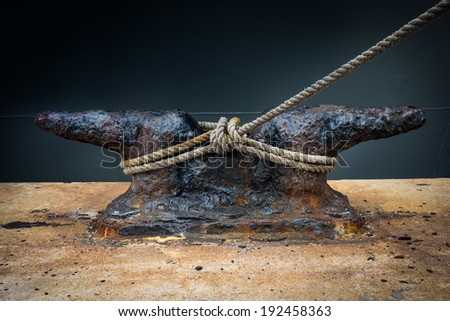 Rusty mooring rope with a knotted end tied around a cleat / Nautical mooring rope - stock photo
