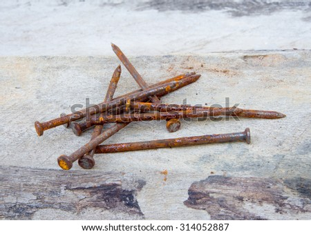 Rusty nails on wood background. - stock photo