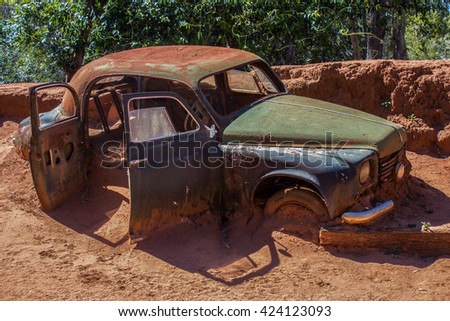 Rusty old abandoned car stuck in the mud in the afternoon sun. - stock photo
