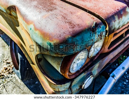 Rusty, old, junked car in the woods - stock photo