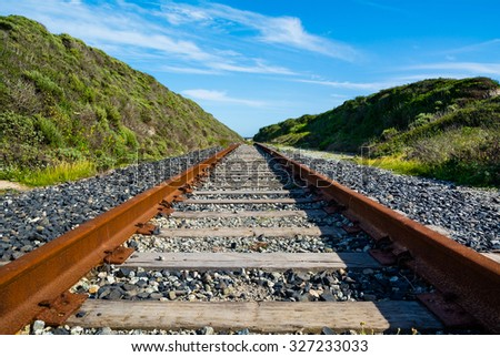 Rusty old railroad goes to horizon - stock photo