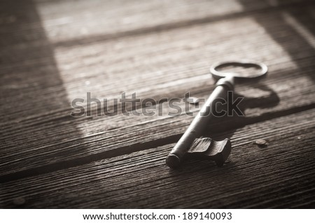Rusty Old Skeleton Key on Dark Rustic Barnwood With Window Light - stock photo