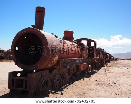 Rusty old steam locomotive and train at the train cemetery in the desert of Bolivia near Uyuni. The trains were imported by the English to be used for mining activities and they were left to rust. - stock photo