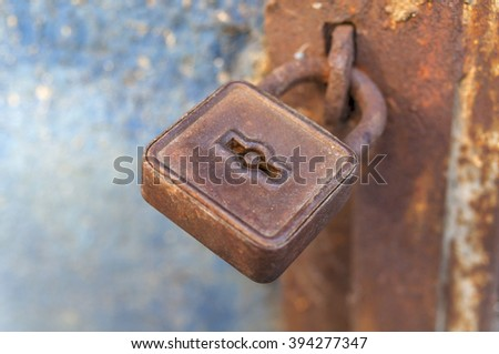 Rusty padlock on the old metal door - stock photo