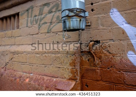 Rusty pipe with flowing rain water. Close up of water gushing out of the pipe. Water flowing from pipe against blurred brick background - stock photo