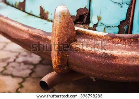 Rusty rear bumper of old blue car - stock photo