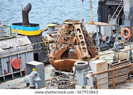 Rusty scoop of cargo crane on the ship deck - stock photo