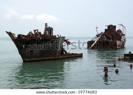 Rusty ships on the sea near the coast in Margarita, Venezuela - stock photo